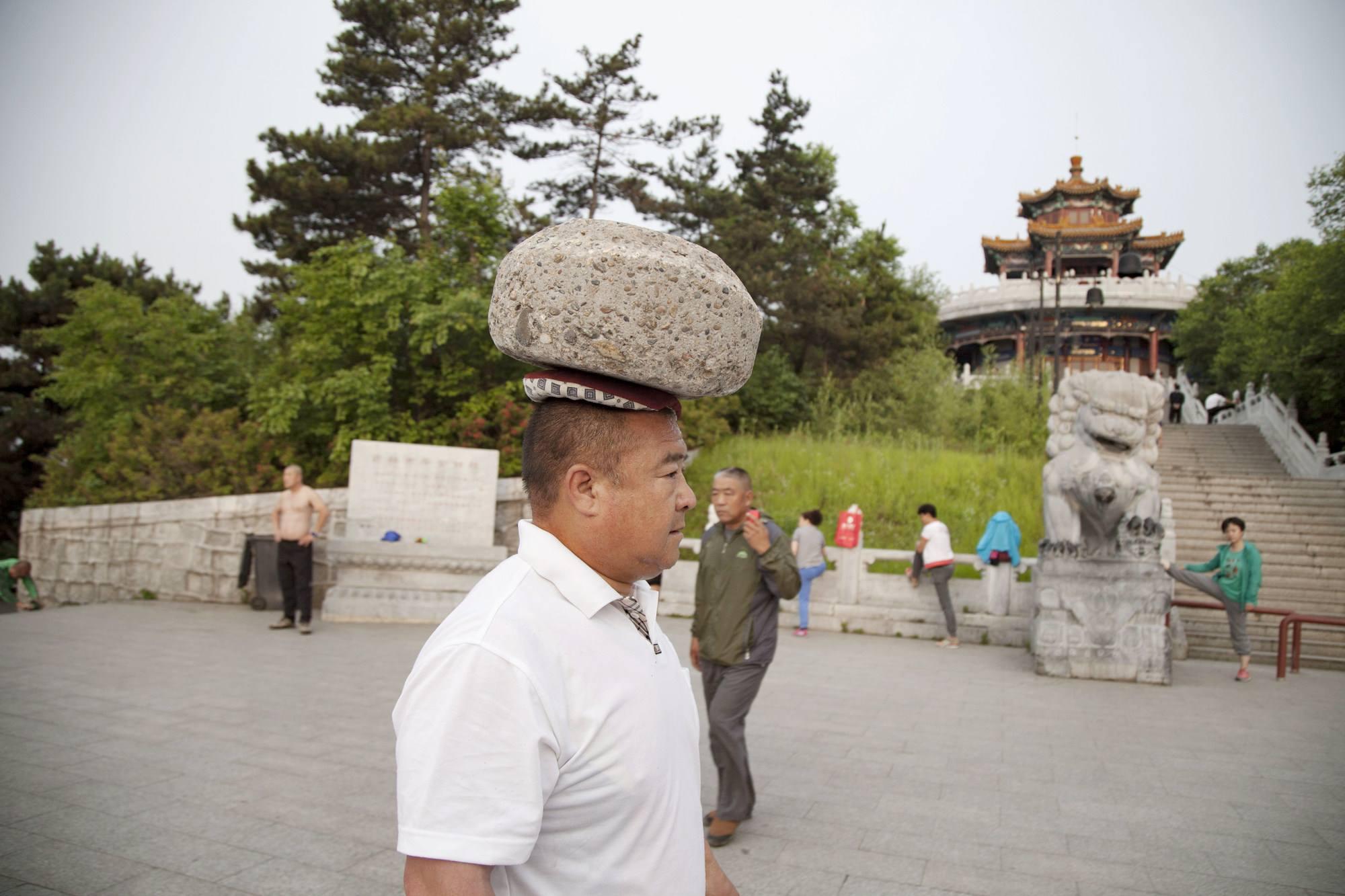 Chine pendant 4 ans  il marche avec une pierre de 40 kg sur la tête pour maigrir!