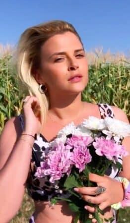 Kelly Vedovelli pose en crop-top sexy au milieu d'un champ de fleurs !