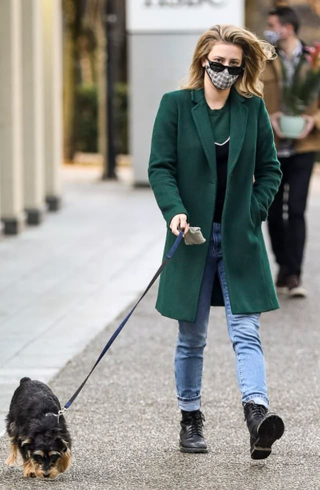 Lili Reinhart très classe masquée dans un manteau vert avec son chien !